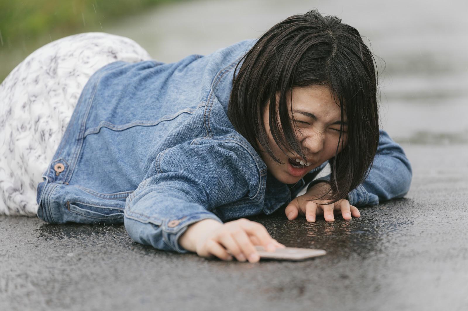 濡れた道路の上で転んで泣いている女性