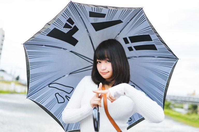 漫画的な「ドン」という擬態語の書かれた傘をさすモデル