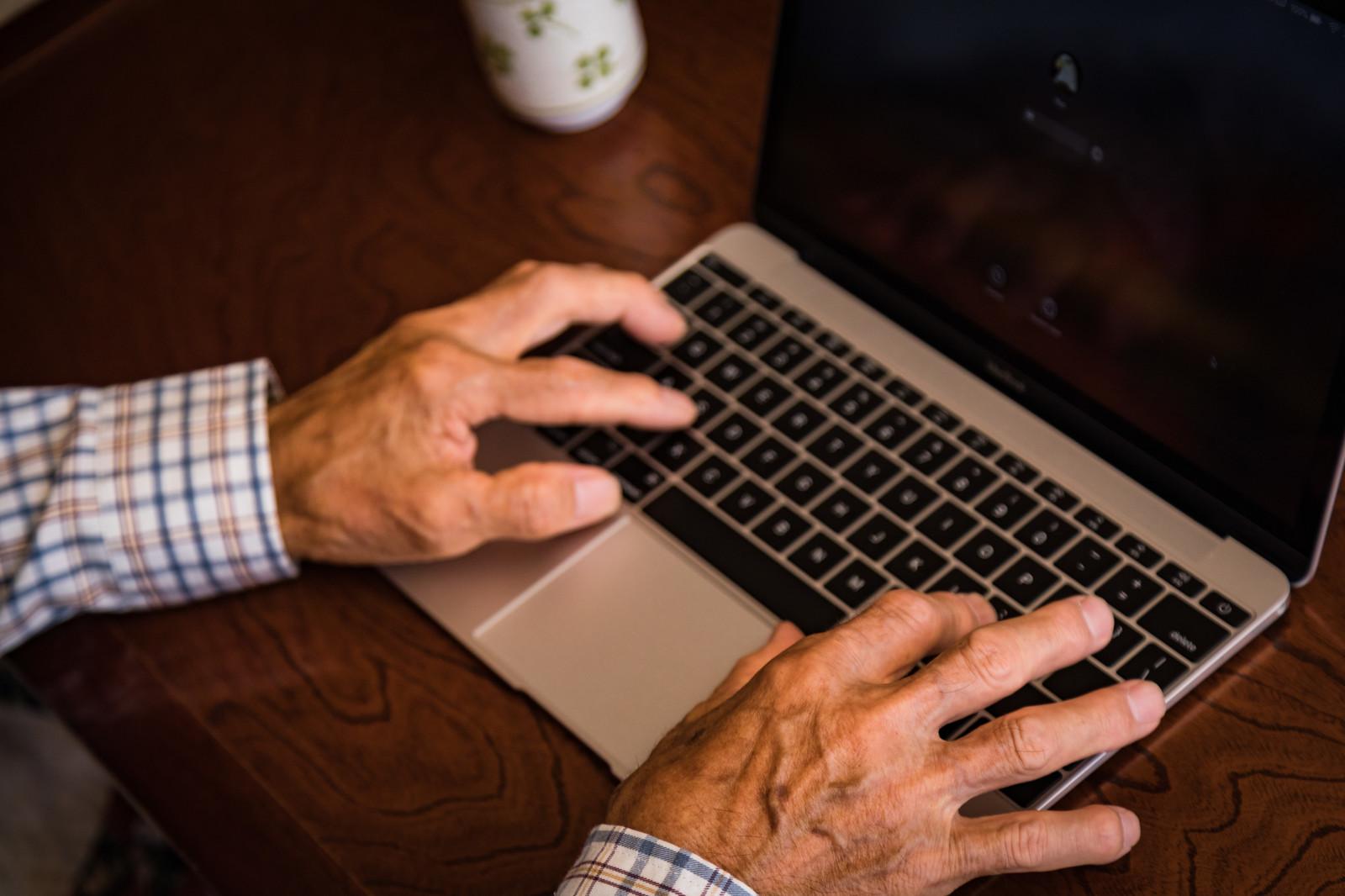 Mac を操作する高齢者の手