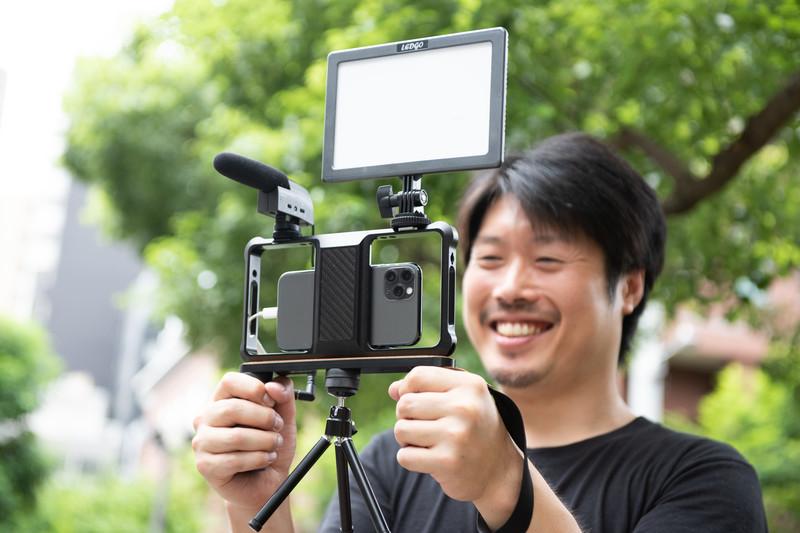 スマホで動画撮影をしつつ笑顔の男性
